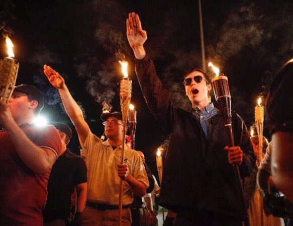 Racists with torches giving Nazi salute